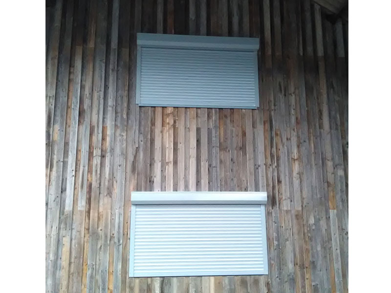 Closed white continental shutters over windows