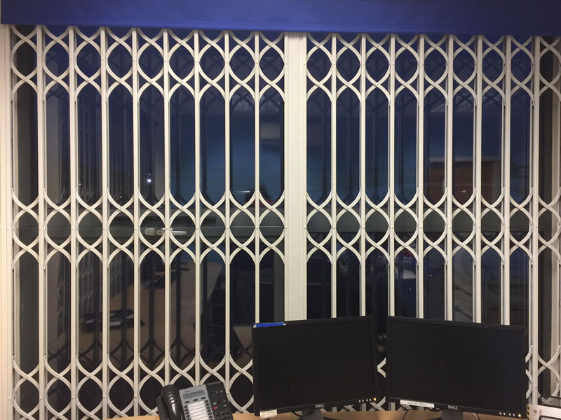Closed white security grills over a window