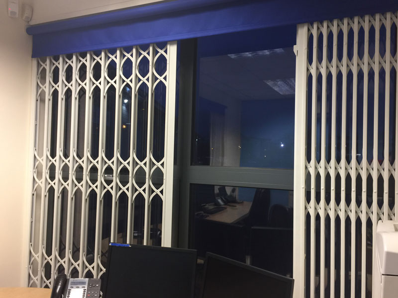 Part open white security grills over a window