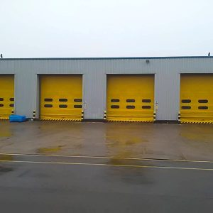 Four hi-speed industrial roll up doors with yellow coating finish in-situ at a warehouse