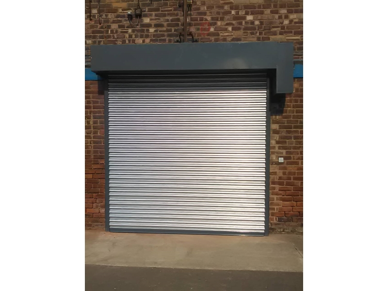 Silver roller shutter pulled down with black canopy