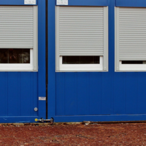 Three silver roller shutters half open on a blue mobile unit.