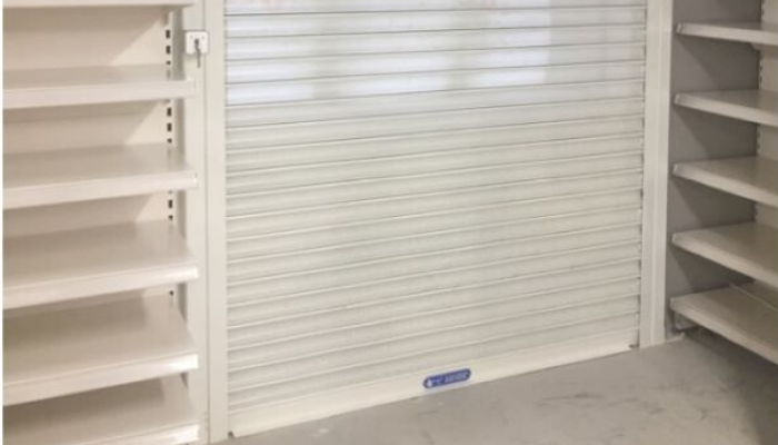 White roller shutters fitted inside a shop